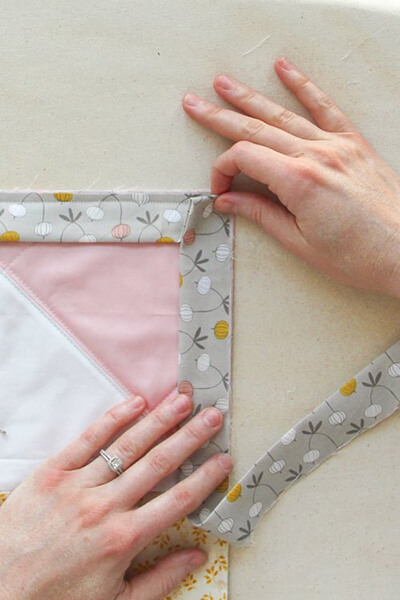 Fold the Mitered Corner Binding Strip Over Itself by Villageboundquilts